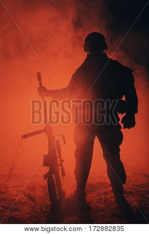 Army sniper with large caliber rifle standing in the fire and smoke. Backlit silhouette, toned image