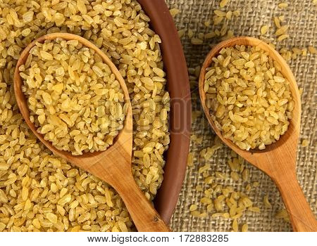 Dry bulgur wheat in a clay bowl with spoon from above on the sacking