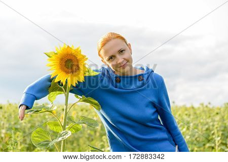 Young red haired woman hugs sunflower in the field