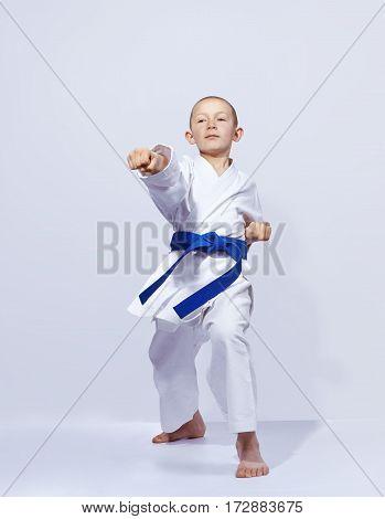 Karateka boy beats punch arm on a light background