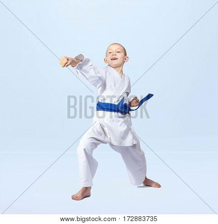 With a blue belt karateka strikes straight punch arm