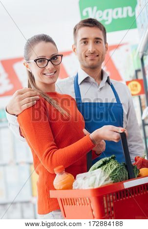 Professional supermarket clerk and happy customer posing together customer care and assistance concept
