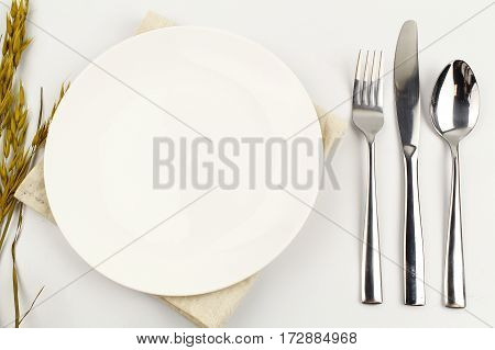 white plate on white background decoration with spoon and fork