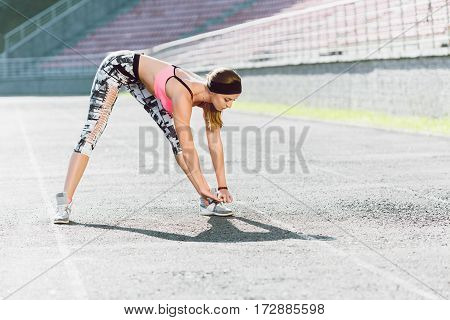 Sport, exercises outdoors. Girl in rose top and black and white leggins doing stretching on stadium. Bending to toes. Full body, profile