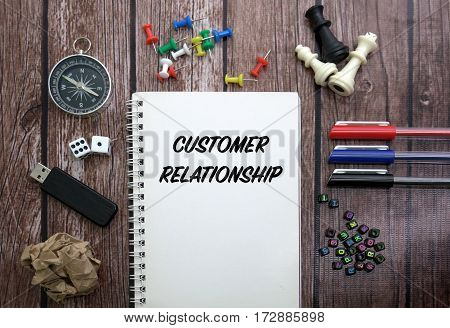 CUSTOMER RELATIONSHIP CONCEPT ON NOTEBOOK WITH STATIONERY
