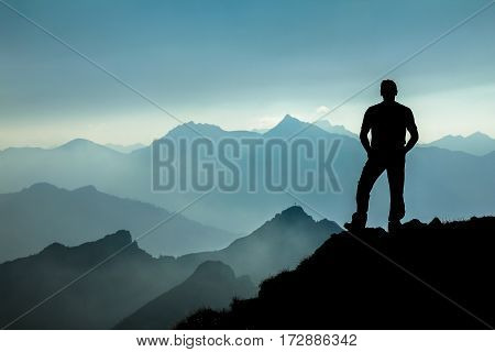 Relaxed man watching dreamfully towards spectacular mountain range silhouettes with bright back light. Tirol, Austria. Bavaria.
