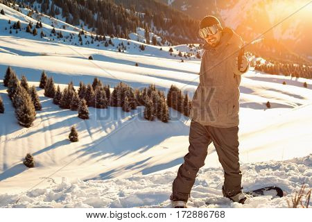 Snowboarder Stands Mountain Top With His Arms Raised