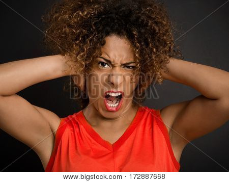 Portrait of an African American woman with hands on the head with a angry face