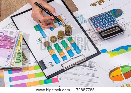 Businesswoman Stacking Euro Coins On Business Graph.