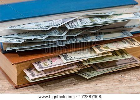 Us 100 Dollar In Book On Desk.