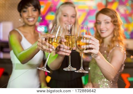 Portrait of three smiling friend toasting glass of champagne at bar