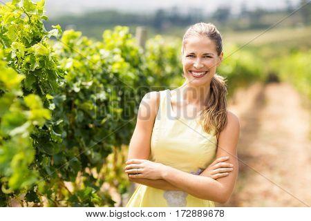 Portrait of female vintner standing with arms crossed in vineyard