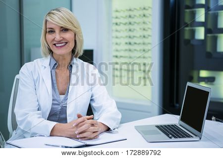 Portrait of smiling female optometrist sitting in ophthalmology clinic
