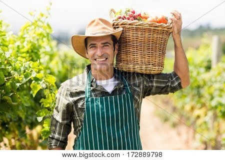 Portrait of happy farmer carrying a basket of vegetables in the vineyard