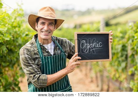 Portrait of a smiling farmer holding an organic sign