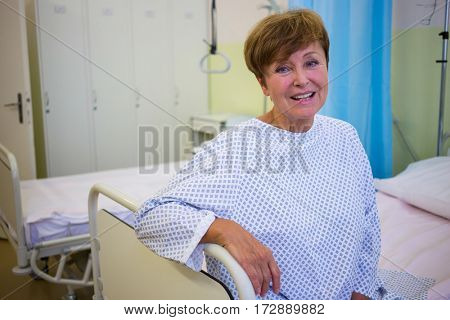 Portrait of smiling senior patient sitting on a bed in hospital room