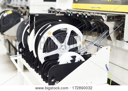 Reels in pick and place chip shooter machine at SMT line used simple package components such as resistors and capacitors for surface mounting at electronic manufacturing factories.