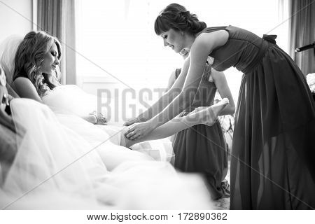 Bridesmaid puts a garter on the bride's leg