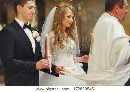 Groom and bride hold priest cassock during an engagement ceremony