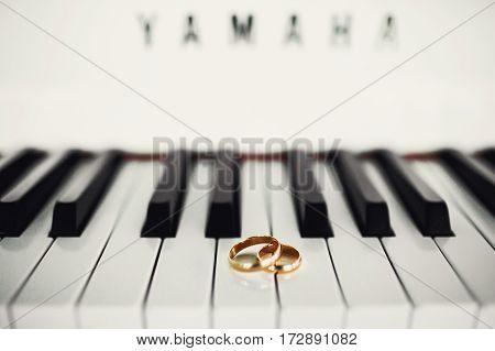 Golden wedding rings lie on white piano keys