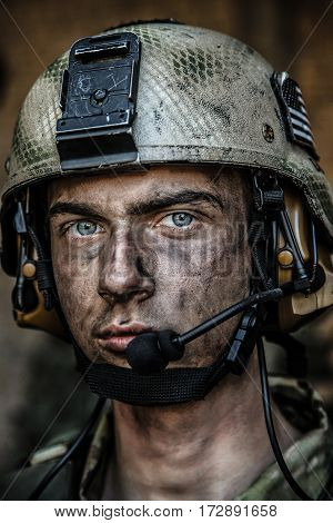 Smoked face of US Army Ranger wearing combat helmet. Closeup portrait. Bright eyes of soldier, young boy at war, sacrifice concept
