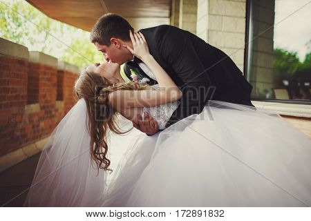 Bride Touches Groom's Head Tenderly While He Bends Her Over Standing On The Balcony