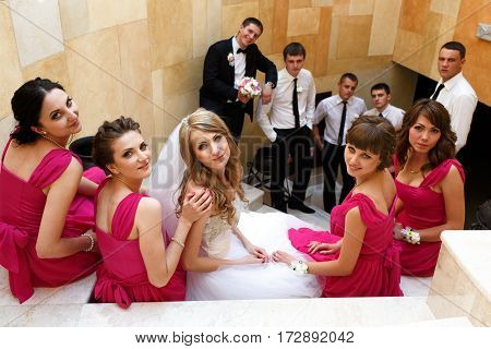 Bride and bridesmaids sit on the white stairs while groom and groomsmen stand behind