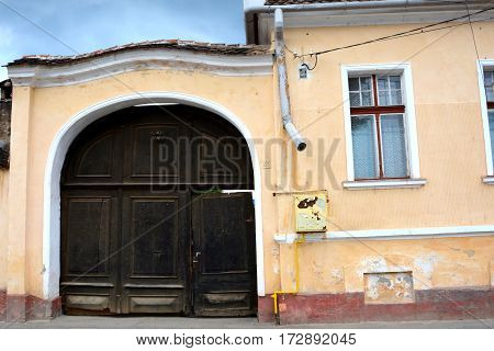 Gate. Typical houses in the village Vulcan (German: Wolkendorf), a commune in Braşov County in the centre of Romania, 16 km west of the county capital Braşov