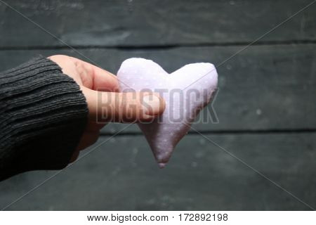 Card for Valentines day, vintage, style, hand holding a heart. Blurred photos for the background..
