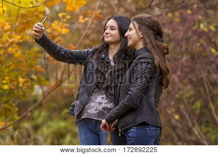 Girlfriends taking selfie picture with smartphone. Friends and friendship concept - happy girls taking picture with smartphone on selfie stick outdoors