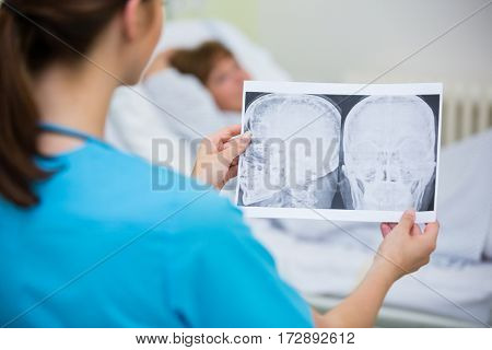 Rear view of nurse checking a x-ray in ward at hospital