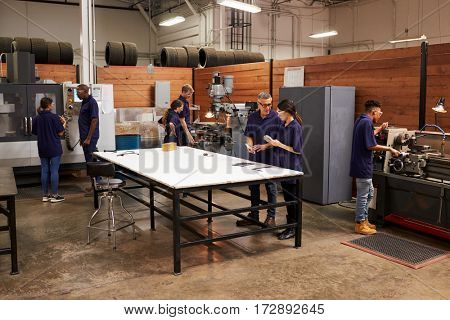 Engineers Working On Machines In Busy Metal Workshop