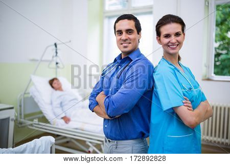 Portrait of smiling doctor and nurse standing with arms crossed in hospital