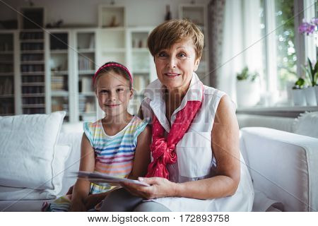 Portrait of senior woman and her granddaughter holding a photo album at home