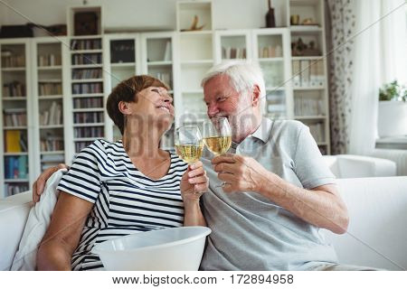 Senior couple toasting glasses of wine in living room