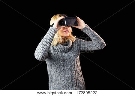 Woman using reality virtual headset against black background