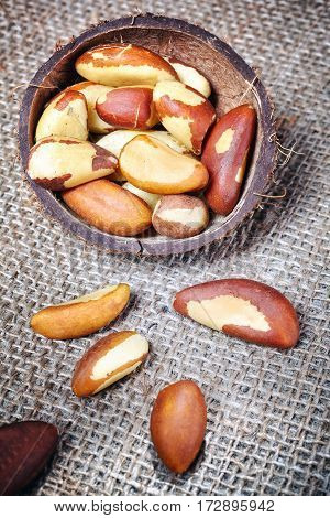 Brazil nuts in a coconut shell on linen background selective focus.