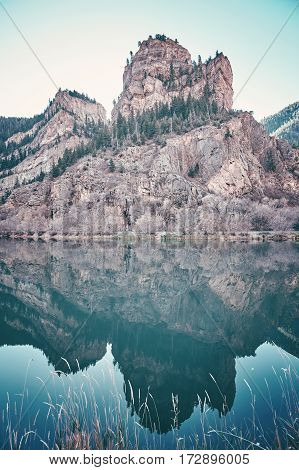 Color toned rocks reflected in water Glenwood Canyon at sunrise Colorado USA.