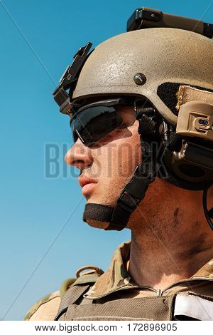 US Army Ranger with weapons in the desert beneath a scorching sun. Closeup face portrait. He is wearing eyewear goggles protection and combat helmet