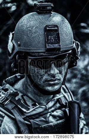 Grimy dirty and tired face of US Army Ranger, young boy wearing eyewear and combat helmet. Closeup
