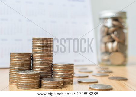 Concept business finance save money Coins stack on wood table with calendar and money in jar