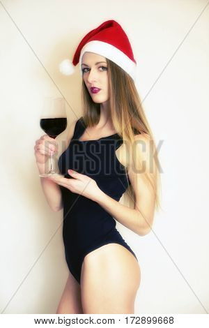 Model thin girl with glass of red wine and santa cap