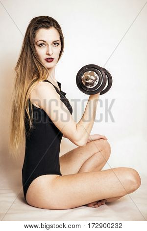 Sitting possing girl with dumbbell in hand.