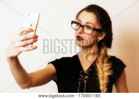 Pretty face young girl in glasses making selfie