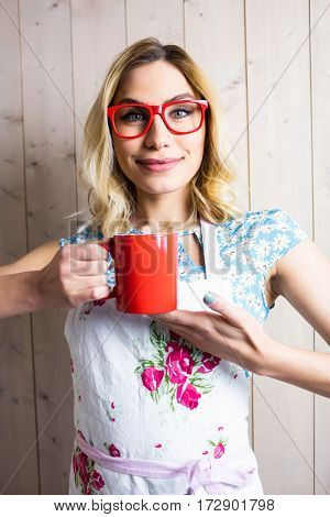 Portrait of smiling woman in apron holding a coffee mug against texture background