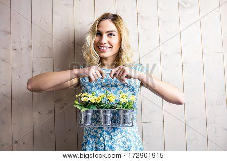 Portrait of smiling woman holding a basket of plant pots against texture background