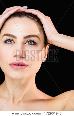 Close-up of beautiful woman posing against black background