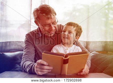 Grandfather and little cute grandson reading book together