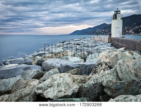 Winter view of the breakwater in the harbour of Camogli (along the shores of Ligurian Sea, Northern Italy), with it lighthouse. Color image.