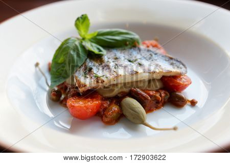 Sea bass fillet with tomato sauce and capers on white plate